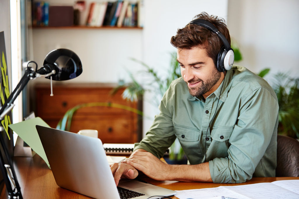 man working remotely with laptop and headphones